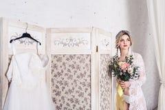 La sposa, vestita in peignoir e biancheria intima, sta lo schermo vicino con il vestito da sposa e tiene il mazzo in sue mani fotografie stock libere da diritti