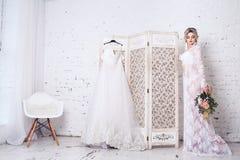 La sposa, vestita in peignoir e biancheria intima, sta lo schermo vicino con il vestito da sposa e tiene il mazzo in sue mani fotografia stock libera da diritti