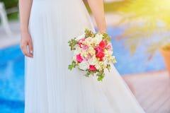 La sposa in vestito da sposa la tiene mazzo di rouses contro la cacca blu Fotografie Stock