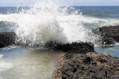 La spuma della costa dell'Oregon spruzza contro roccia nera Immagini Stock
