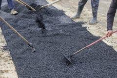 La squadra della costruzione di strade ha utilizzato le pale per spargere più asfalto immagini stock