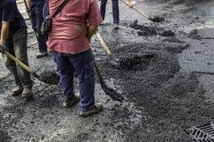 La squadra della pavimentazione spande l'asfalto con le pale 2 immagini stock