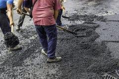 La squadra della pavimentazione spande l'asfalto con le pale fotografia stock