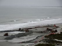 La squadra di costruzione lavora per preparare la spiaggia davanti alla tempesta fotografia stock