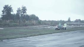 La squadra di Moto conduce la bici fuori dalla pista dopo la caduta dello sportivo stock footage