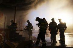 La squadra di vigili del fuoco che combattono con il fuoco Fotografia Stock Libera da Diritti