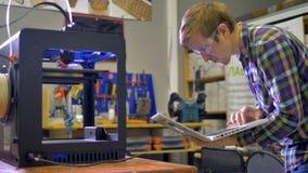 La stampante 3d sta funzionando e l'uomo sta esaminando lo schermo del computer portatile 4K video d archivio