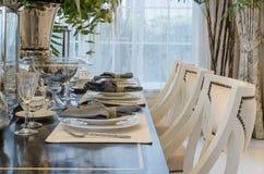 La stanza dinning del lusso con la tavola ha messo sulla tavola di legno a casa Immagine Stock Libera da Diritti