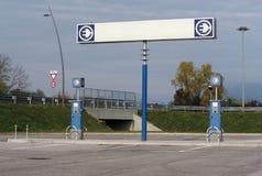 La station de charge de voiture électrique avec un grand panneau routier vide au-dessus du réapprovisionnement en combustible se  Images stock