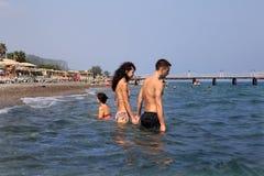 La station de vacances turque, couple entre profondément dans l'eau de mer tenant des mains Photographie stock