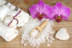 La station thermale a placé avec la lotion de corps, le sel de bain, le blanc, la fleur rose d'orchidée et les pierres sous forme Photographie stock