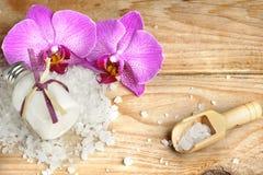 La station thermale a placé avec la lotion de corps, le sel de bain, le blanc, la fleur rose d'orchidée et les pierres sous forme Photos stock