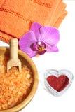 La station thermale a placé du sel de bain orange, de la serviette avec la fleur d'orchidée et du coeur rouge le jour du ` s de V Photographie stock libre de droits