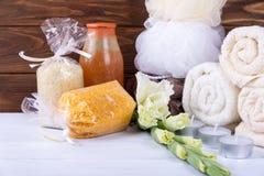 La station thermale réglée avec des fleurs, sel de mer, douche de gel, serviettes, frotte et mèche sur la table en bois blanche A photo libre de droits