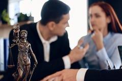 La statua bronzea di Themis tiene la bilancia della giustizia Nel fondo unfocused, l'adulto firma i documenti fotografie stock