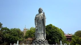 La statua d'argento di Buddha sta sul piedistallo contro la pagoda stock footage
