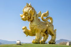 La statua del leone dorato su un campo con il fondo del cielo blu, al parco Chiangrai di Singha Fotografie Stock Libere da Diritti