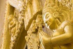 La statua dell'oro delle donne prega in tempio Ubonratchathani Tailandia fotografia stock libera da diritti