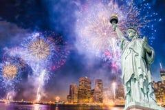 La statua della libertà con fondo vago di paesaggio urbano con i bei fuochi d'artificio alla notte, Manhattan, New York Immagini Stock Libere da Diritti