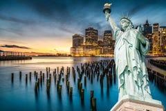 La statua della libertà con il fondo del Lower Manhattan nella sera Fotografie Stock