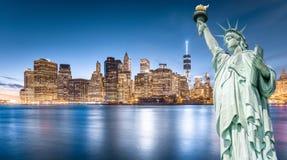 La statua della libertà con il fondo del Lower Manhattan nella sera Fotografia Stock