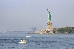 La statua della libertà con nei precedenti i porti del New Jersey, New York, Stati Uniti fotografia stock libera da diritti