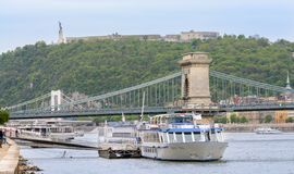 La statua della libertà e la cittadella sono situate alla cima della collina di Gellert, il più alto punto di Budapest il ponte s fotografia stock libera da diritti