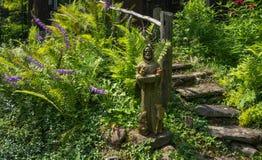 La statua dello St Francis vi accoglie favorevolmente ad una casa nel legno Immagini Stock Libere da Diritti