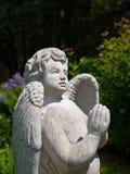 La statua di pietra di angelo con pregare passa lo sguardo verso il cielo Immagini Stock Libere da Diritti