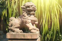 La statue chinoise de lion dans un temple de porcelaine avec le vert pousse des feuilles backgroud photographie stock libre de droits