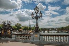 La statue d'or et l'éclairage signalent orner le pont d'Alexandre III au-dessus de la Seine et Tour Eiffel à Paris Photos stock