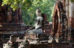 La statue de Bouddha dans la posture de méditation avec la lumière du soleil émettant du ciel pour illustrer un regard de sage, d Photographie stock libre de droits