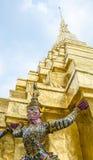 La statue de démon soutenant la pagoda d'or Photographie stock libre de droits