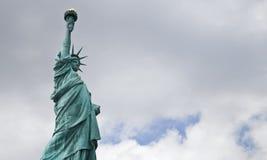La statue de Liberty Against un ciel nuageux Images libres de droits