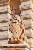 La statue de lion avec le manteau des bras s'approchent de la voie de base, Mdina Images stock