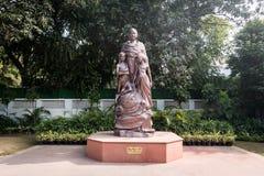 La statue de Mahatma Gandhi avec des enfants en bronze se tenant dans la cour Photographie stock libre de droits