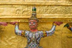 La statue géante soutenant la pagoda d'or dans le temple d'Emerald Buddha (Wat Phra Kaew), Bangkok, Thaïlande Photos libres de droits