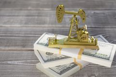 La stazione d'oscillazione della perforazione della pompa di olio sta sui pacchi delle banconote del dollaro immagini stock