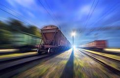 La stazione ferroviaria con i vagoni del carico ed il treno si accendono nel moto Immagine Stock Libera da Diritti
