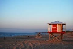 La stazione rossa del bagnino aspetta silenziosamente su una spiaggia abbandonata Fotografia Stock Libera da Diritti