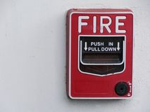 La stazione rossa di tirata dell'allarme antincendio installa sulla parete bianca Immagine Stock