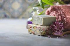La stazione termale di concetto Sapone fatto a mano, asciugamani, fiori e sale marino immagini stock