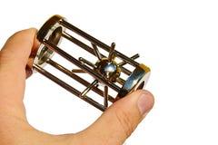 La stella appuntita di puzzle meccanico in gabbia d'acciaio ha tenuto in mano sinistra su fondo bianco Immagini Stock