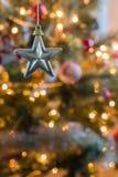 La stella a cinque punte ciondola davanti all'albero di Natale variopinto Fotografia Stock Libera da Diritti