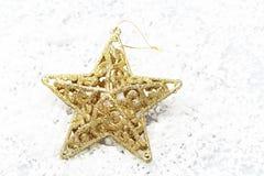 La stella d'oro su neve per natale della decorazione Fotografia Stock Libera da Diritti