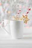 La stella del pan di zenzero ha messo sopra una tazza bianca con cioccolata calda sui precedenti di bokeh e di neve Immagine Stock Libera da Diritti