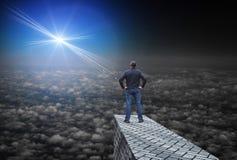 La stella luminosa lontana illumina l'oscurità e l'uomo che sta sopra le nuvole Immagini Stock