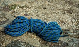 La stenditura rampicante blu della corda ha piegato su una roccia fotografia stock
