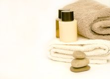 La Stone Spa. Still life on white spa towels and massage oil and lotion Stock Photography