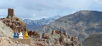 La strada al monastero buddista di Basgo: nella priorità alta ci sono stupas tibetani dei fiori gialli e blu, nel backgro Fotografie Stock Libere da Diritti